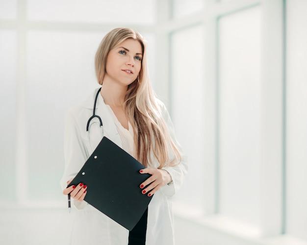 Thérapeute avec un presse-papiers, debout près de la fenêtre de l'hôpital