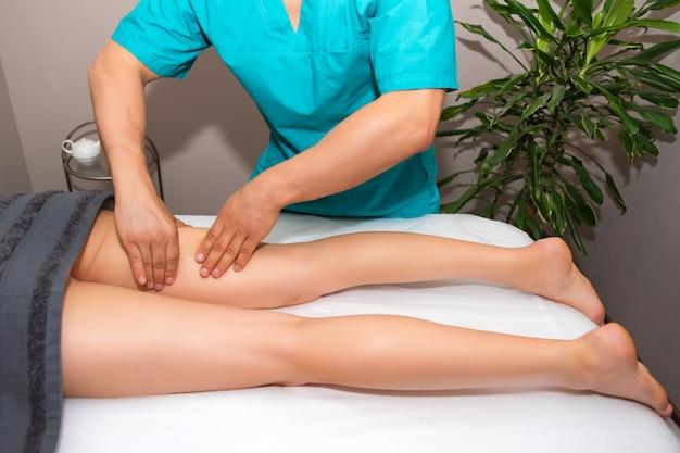Thérapeute professionnel donnant un massage relaxant des jambes à une femme au spa.