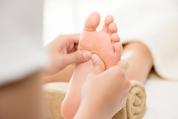 Thérapeute professionnelle donnant un massage thaï traditionnel à une femme