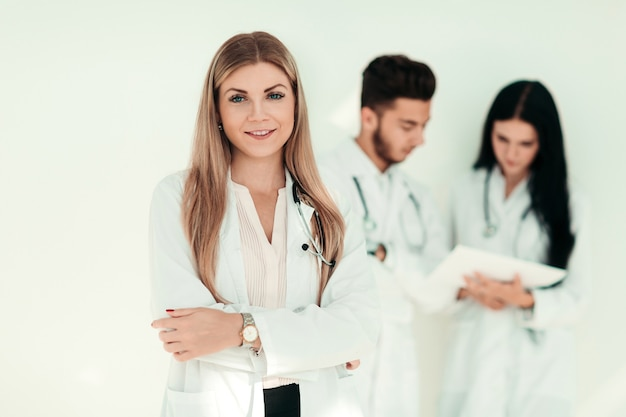 Thérapeute sérieux avec un presse-papiers en se tenant debout en clinique