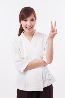 Thérapeute spa femme pointant vers le haut 2 doigts, comptage, numérotation, signe de la main de la victoire
