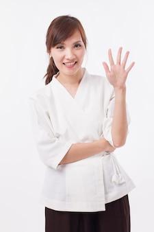 Thérapeute spa femme pointant vers le haut de 5 doigts, comptage, numérotation