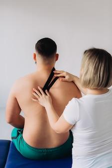 Un thérapeute tape du ruban adhésif sur le cou du patient.