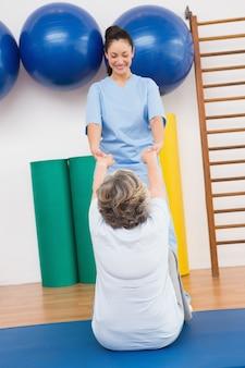Thérapeute travaillant avec une femme senior sur un tapis d'exercice