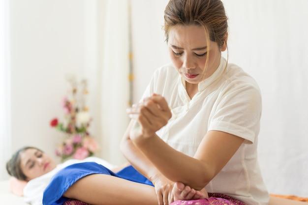 Thérapeute utilise son coude pour masser un pied de femme
