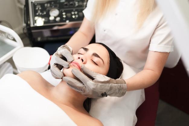 Thérapie aux micro-courants. cosmelotologist fait un massage facial stimulant avec des gants électriques.
