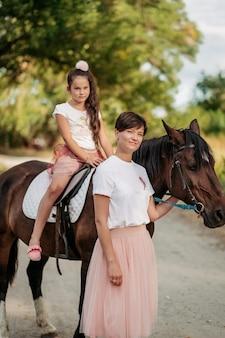 Thérapie d'enfant pour une promenade avec un cheval. contact émotionnel avec le cheval. promenade mère et fille en été dans le parc avec un cheval.