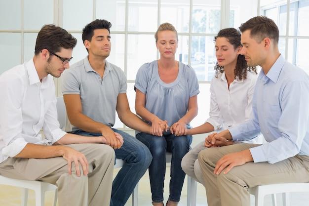 Thérapie de groupe en séance assis dans un cercle, tenant par la main