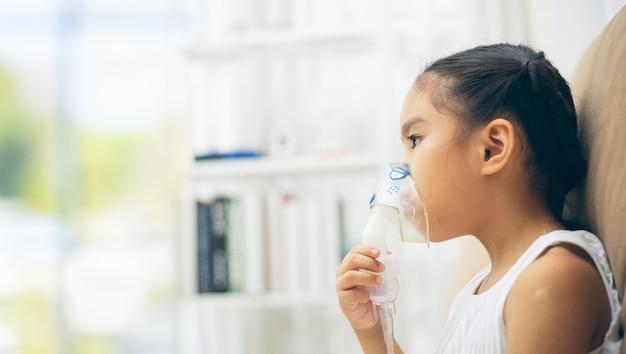 Thérapie d'inhalation de l'enfant par le masque de l'inhalateur avec la fumée douce de bronc