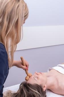 Thérapie madero, massage relaxant anti-âge - mains du masseur massant le front de la jeune fille à l'aide d'un masseur en bois naturel. massage lifting du visage, correction et élimination des rides mimiques