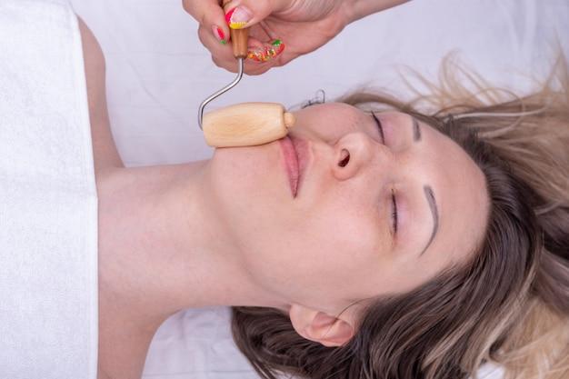 Thérapie madero, massage relaxant anti-âge - mains du masseur massant les lèvres de la fille à l'aide d'un masseur en bois naturel. massage lifting du visage, correction et élimination des rides mimiques