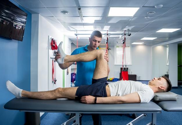 Thérapie de réadaptation. physiothérapeute travaillant avec un jeune patient de sexe masculin