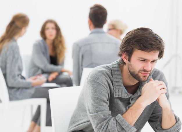 Thérapie en séance assis dans un cercle alors que l'homme au premier plan