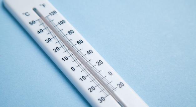 Thermomètre blanc sur fond bleu.