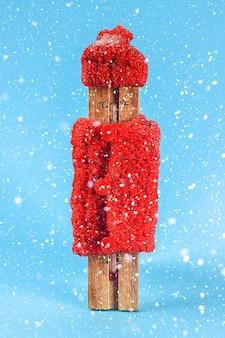 Thermomètre en bois, portant un chapeau rouge et un pull sur un fond bleu