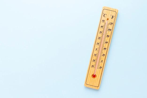 Un thermomètre classique en bois sur fond bleu n'affiche aucune température. espace de copie