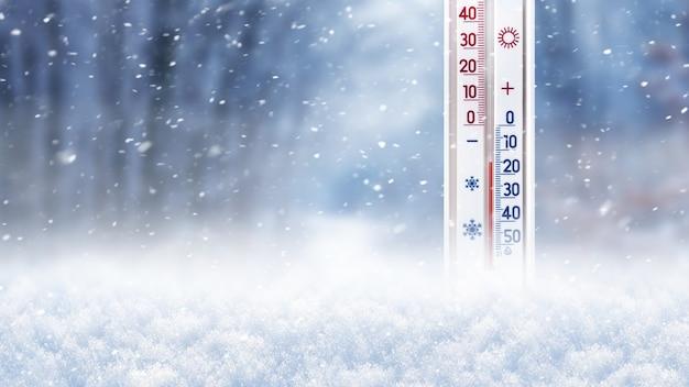 Le thermomètre dans la neige sur un fond d'arbres pendant une chute de neige montre 15 degrés au-dessous de zéro