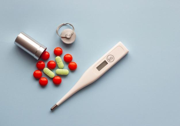 Thermomètre électronique et pilules de couleur sur fond bleu