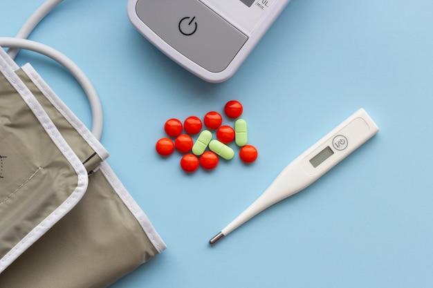 Thermomètre électronique et tonomètre avec pilules sur fond bleu