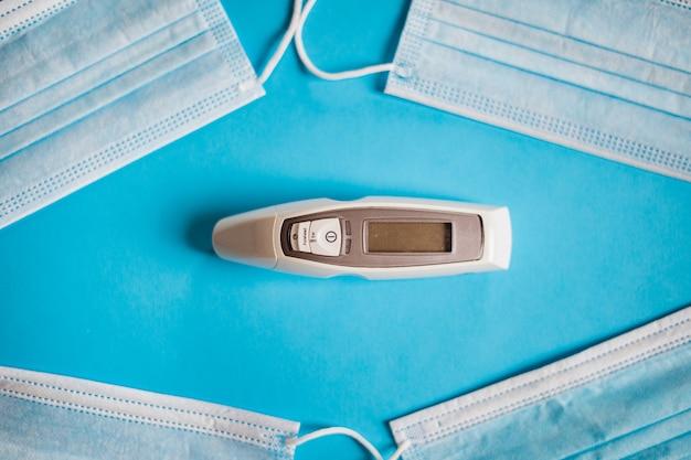 Un thermomètre entouré de quatre masques chirurgicaux protection coronavirus