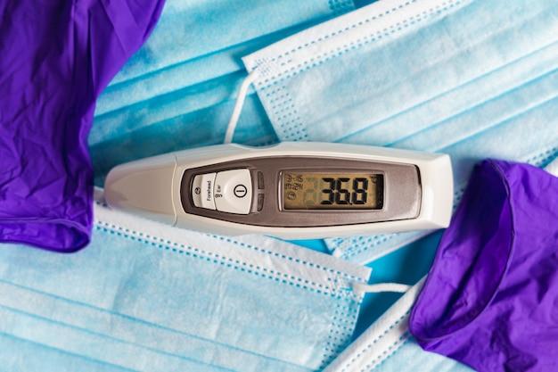 Thermomètre entouré d'un tas de masques chirurgicaux et de gants médicaux protection covid vue de dessus