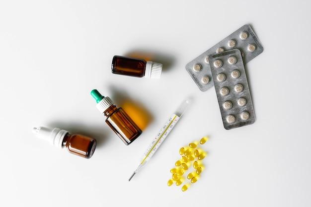 Thermomètre, gouttes nasales, pilules et capsules de vitamines sur fond blanc. maladie et traitement. pharmacie