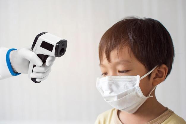 Thermomètre infrarouge médical mesurant la température du petit garçon asiatique patient