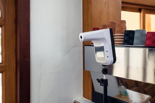 Thermomètre infrarouge de réglage sans contact sur le devant du magasin de comptoir