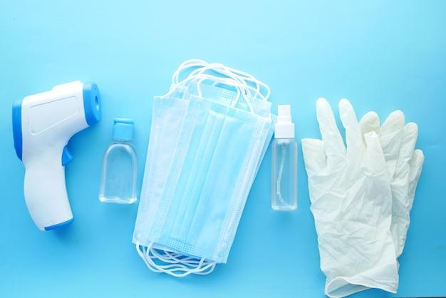 Thermomètre de masques chirurgicaux et désinfectant pour les mains sur une surface bleue