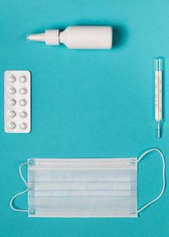 Thermomètre médical, masque de médecine, gouttes et pilules sur bleu.