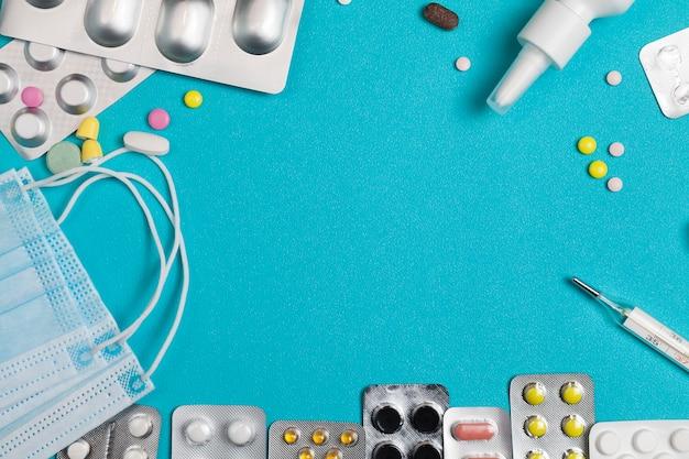 Thermomètre médical, médicaments, gouttes et pilules sur bleu.