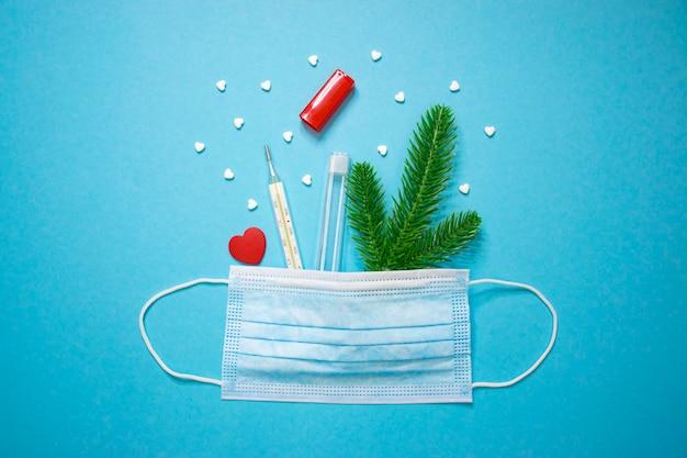 Thermomètre à mercure en verre avec des pilules coeur rouge et branche d'épinette en masque de protection médicale sur fond bleu