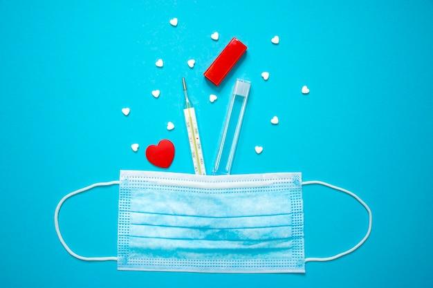 Thermomètre à mercure en verre avec des pilules en forme de coeur et coeur rouge dans un masque de protection médicale sur fond bleu