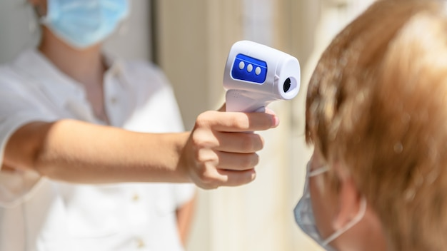 Thermomètre numérique numérisant la température corporelle d'un garçon