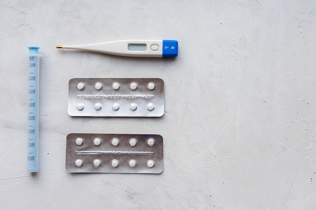 Thermomètre, pilules et antipyrétiques pour les premiers symptômes du coronavirus