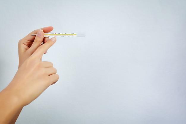 Thermomètre pour mesurer la température corporelle en main. concept de médecine et de soins de santé