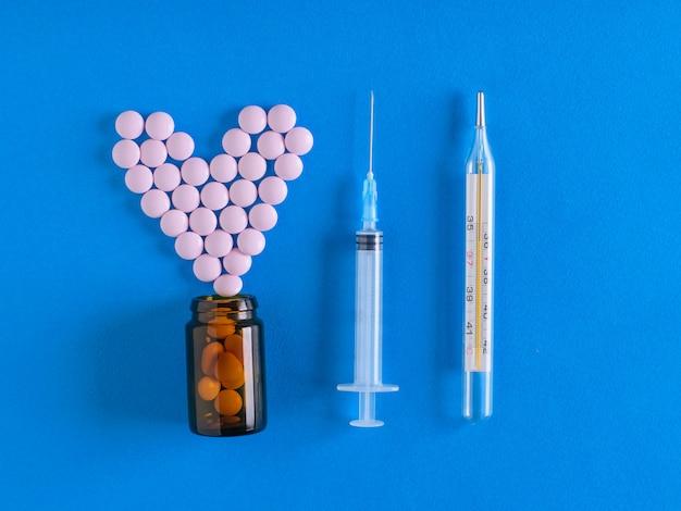 Thermomètre, seringue et pilules renversées de la bulle en bleu.