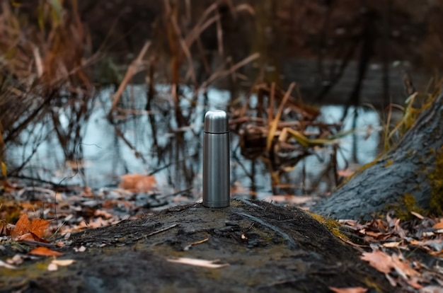 Thermos en acier de voyage debout au bord du lac. étang d'automne