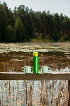 Thermos avec deux tasses préparées pour la journée de camping