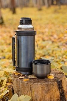 Thermos et tasse de thé chaud sur une souche dans la forêt d'automne - image