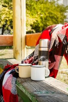 Thermos avec thé chaud sur une table en bois.