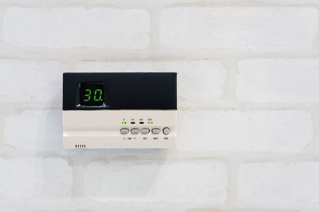 Thermostat de programmation moderne devant le mur de briques blanches avec surface et texte