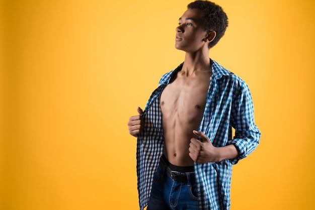Thin adolescent afro-américain montre torse nu.