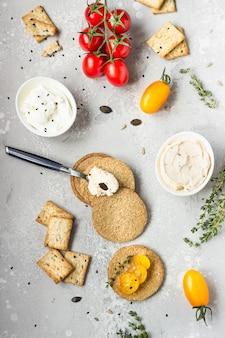Thin craquelins de grains entiers croustillants avec du fromage à la crème et les tomates sur une plaque noire.