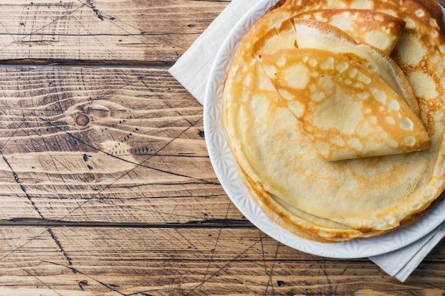 Thin pancakes sur une assiette. fond en bois espace de copie