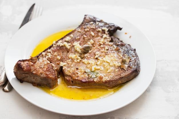 Thon frit à l'ail, la feuille de laurier et l'huile d'olive sur plaque blanche