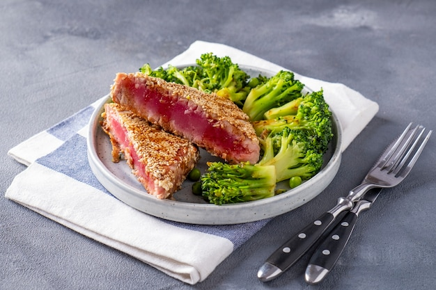 Thon frit aux légumes servi avec fourchette et couteau