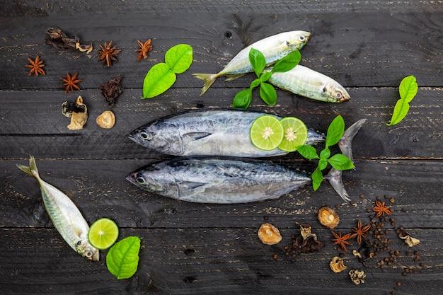 Thon listao frais sur bois noir foncé. poisson aux épices et légumes
