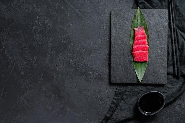 Thon sashimi sur une planche en pierre. vue de dessus. fond de fond