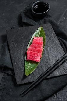 Thon sashimi sur une planche en pierre. vue de dessus